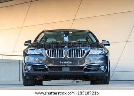MUNICH, GERMANY - DECEMBER 27, 2013: New modern model of BMW 535d luxury power class station wagon. Wet after the rain dark grey metallic car. - stock photo
