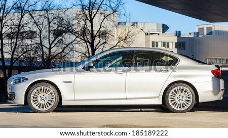 MUNICH, GERMANY - DECEMBER 27, 2013: Sideview of new modern model BMW 535i sedan. Wet after the rain prestige business class car. - stock photo