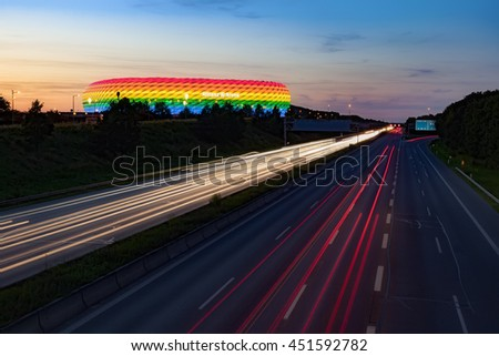 MUNICH, GERMANY - JULY 9, 2016: Long exposure of a highway at night with Allianz Arena, colored in rainbow colors for CSD weekend, Munich, Bavaria, Germany - stock photo