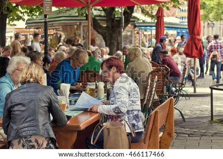 MUNICH, GERMANY - JUNE 14, 2016 - People have leisure time, Bavarian food and beer at open air beer garden in Viktualienmarkt, gourmet market and touristic attraction in Munich center