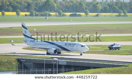 Munich, Germany - May 6, 2016: Airplane Boeing 737-800 by El Al Israel Airlines landed in international airport and escorted by armed police armored vehicle provides anti terrorism security measures. - stock photo