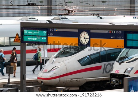 MUNICH, GERMANY -  MAY 25, 2010: Munich main central train station platform view, with a high speed ICE train, timetable, running travelers clock on platform at Hauptbahnhof on May 25, 2010 in Munich.