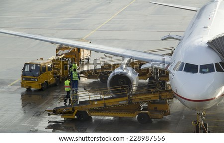 Munich, Germany - October 16, 2014: Ground crew refueling and working below a passenger airplane. - stock photo