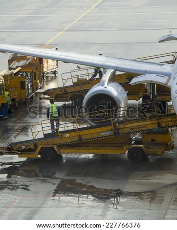 Munich, Germany - October 16: Ground crew refueling and working below a passenger airplane in  Munich, Germany on October 16, 2014 - stock photo