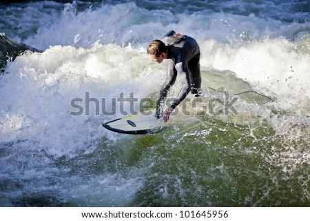 MUNICH, GERMANY - OCTOBER 23: Unidentified surfer in the Eisbach river in English Garden in Munich, Germany at October 23, 2011. The first surfers discovered the Eisbach in the 1970's.