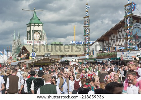 MUNICH, GERMANY - SEPT. 21, 2014: Crowds of visitors at the 181st Oktoberfest celebrating the festivities. The Festival runs from Sept. 20 - Oct. 5  in Munich, Germany - stock photo