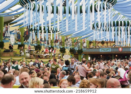 MUNICH, GERMANY - SEPT. 21, 2014:  Oktoberfest Crowds of visitors at the Spatenbrau Tent celebrating the festivities. The Festival runs from Sept. 20 - Oct. 5  in Munich, Germany - stock photo