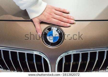 MUNICH, GERMANY - SEPTEMBER 19, 2012: Female hand and logotype BMW on new model prestige car. - stock photo