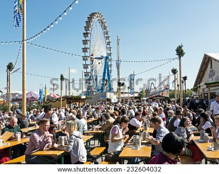 MUNICH, GERMANY - SEPTEMBER 21 - People at the Oktoberfest - they are sitting in a typical beergarden - at the background a carousel - the photo was taken at September 21, 2011 in Munich (Germany). - stock photo