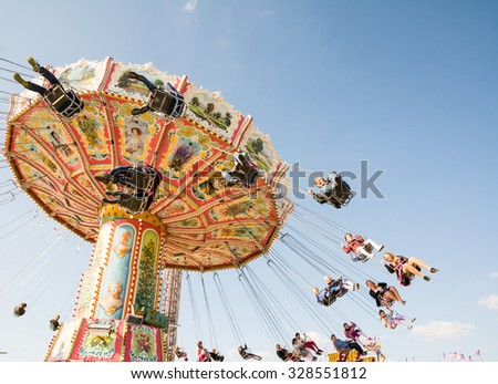 MUNICH, GERMANY - SEPTEMBER 30: People in a chairoplane on the Oktoberfest in Munich, Germany on September 30, 2015. Oktoberfest is the biggest beer festival of the world with over 6 million visitors. - stock photo