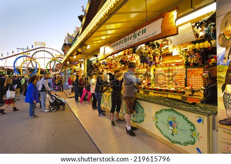 MUNICH, GERMANY - SEPTEMBER 23, 2014: The Oktoberfest in Munich is the biggest beer festival of the world. The visitors have lot of fun with many amusement huts and shops for food and souvenirs. - stock photo