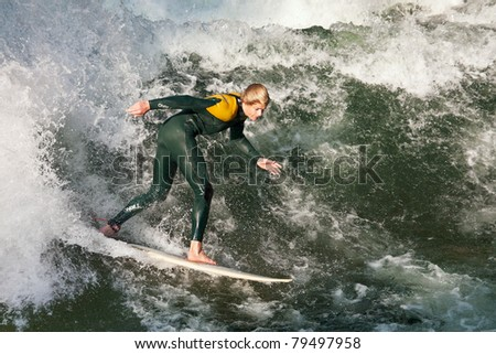 MUNICH, GERMANY - SEPTEMBER 28: Unidentified surfer riding the Eisbach standing wave on September 28, 2009 in Munich, Germany. The small man-made river runs through the Englischer Garten park. - stock photo