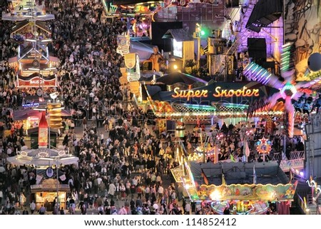 MUNICH - SEPTEMBER 28: The lights of the world's famous fun fair and beer festival Oktoberfest attract crowds of visitors from all over the world on the night of September 28, 2012 in Munich, Germany. - stock photo