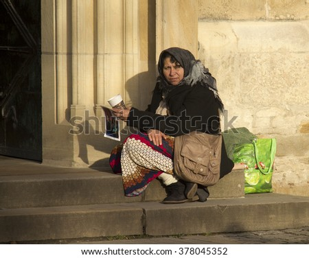 Munster, Germany - December 23, 2015: Female beggar sits at the entrance of the Munster Saint Paul's Dom in Munster, Germany on December 23, 2015 - stock photo