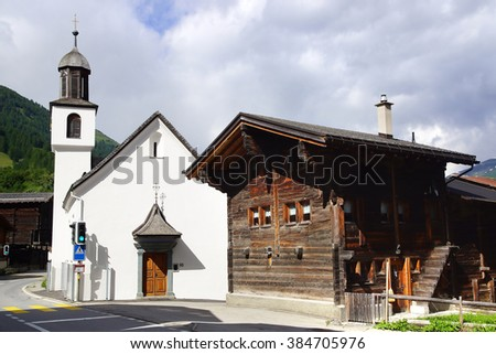 MUNSTER, SWITZERLAND- JUNE 20, 2015: The ancient traditional chalet and Church along the Furkastrasse. Floral decoration on the facades in historic medieval old town.
