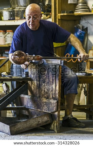 MURANO, ITALY - AUGUST, 5, 2015: Glass worker in action in the Murano glass factory. - stock photo