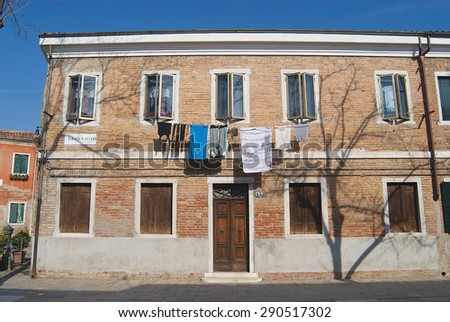 MURANO, ITALY - FEBRUARY 27, 2007: Exterior of the facade of a residential building with washed clothes hanging outside in Murano, Italy. - stock photo