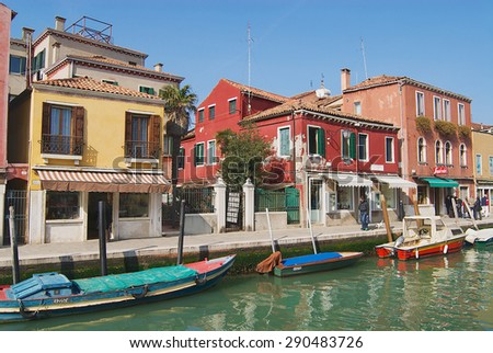 MURANO, ITALY - FEBRUARY 27, 2007: View to the channel, boats, buildings and people at the street in early spring in Murano, Italy. - stock photo