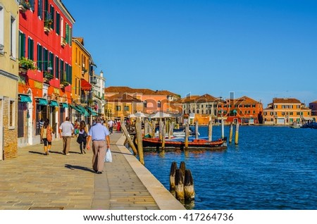 MURANO, ITALY, SEPTEMBER 20, 2015: people are walking down a quay of murano island in italy - stock photo