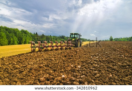 MURANOVO, MOSCOW REGION, RUSSIA - AUGUST 08, 2014. Farmers plow the field after harvesting the crop - stock photo