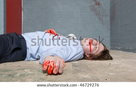 Murder victim lying on the floor, being shot in a basement, with blood splatter on the wall - stock photo