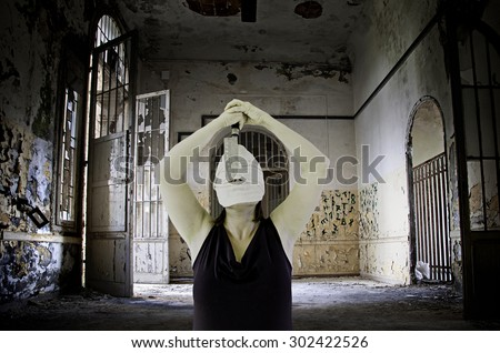 Murderer in abandoned house with a knife, halloween - stock photo