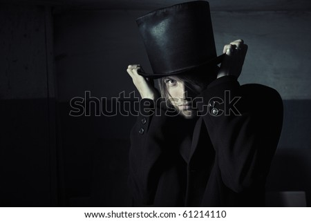 Murderer in black coat and top hat in the dark interior. Natural darkness and artistic colors added - stock photo