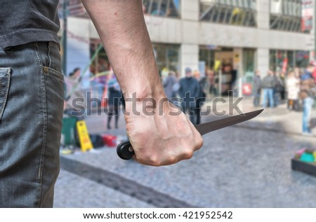 Murderer or killer is attacking with knife n public place. - stock photo