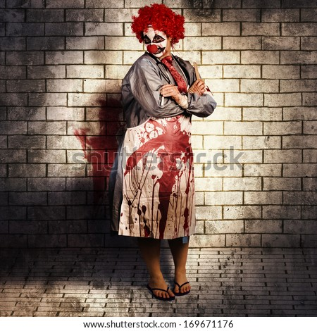 Murderous monster clown standing in full length on brick illustration background with blood stained apron. Killing medical practice - stock photo