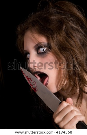 Murderous woman with very scary eyes licking the blood of her knife - stock photo