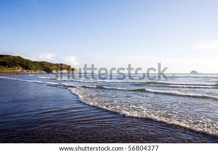 Muriwai Beach on a bright sunny evening with people playing in the surf - stock photo