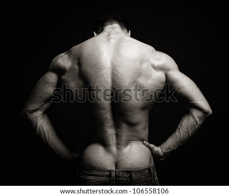 muscle man back on black background - stock photo