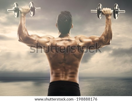 Muscle man lifting weights on outdoor - stock photo