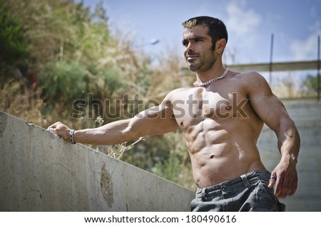Muscle man shirtless outdoors leaning against concrete wall. Ripped abs, pecs and muscular arms - stock photo