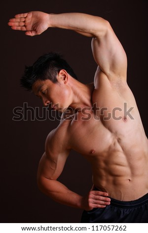 Muscle man stretching left arm and abs on black bacground - stock photo