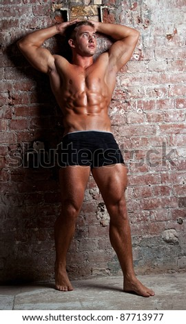 Muscle sexy young naked boy in black shorts leans on a brick wall - stock photo