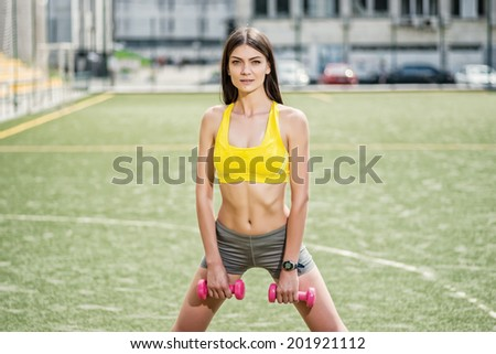 Muscle training with dumbbells. Young and slim woman trains with dumbbells outdoors on the football field. - stock photo