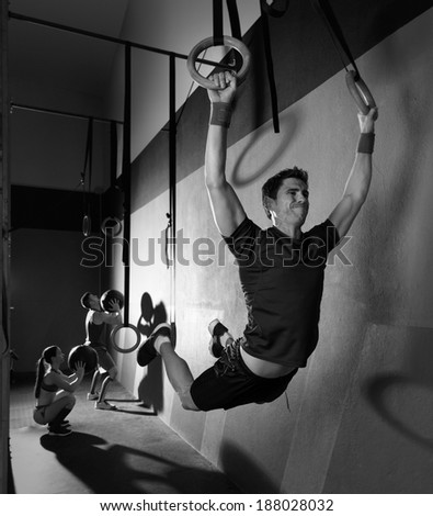 Muscle ups rings man swinging workout exercise at gym - stock photo