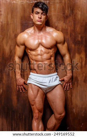 Muscle young man on wooden background. - stock photo