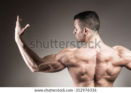 Muscled back and hand of athletic man - studio shot