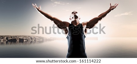 Muscled fitness triathlon athlete. Arms spread wide. Victory. Standing near lake. - stock photo
