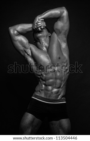 Muscled male model in expressive pose - stock photo