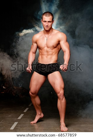 Muscled male model posing in studio with a smoke - stock photo