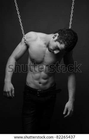 Muscled male model posing with chains - stock photo