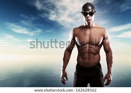 Muscled swimmer man with cap and glasses outdoor at a lake with blue cloudy sky. Extreme fitness sport. - stock photo