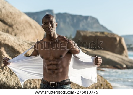 Muscular African american black male model, ripping his white vest shirt on the beach with great power and anger - stock photo