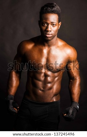 Muscular african guy wearing sporty gloves ready for a fight.