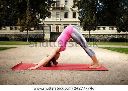 Muscular and experienced yoga woman trainee exercising workout in city park - stock photo