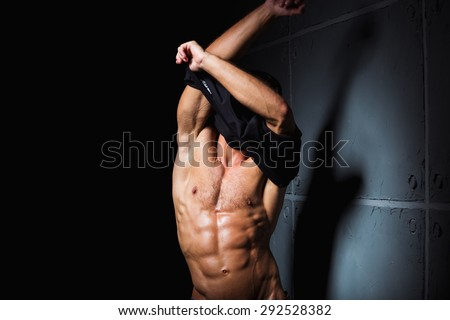 Muscular and sexy torso of young man with perfect abs taking off his shirt - stock photo