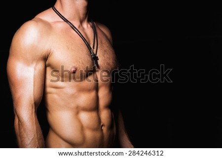 Muscular and sexy torso of young sporty man bodybuilder with perfect abs and chest - stock photo